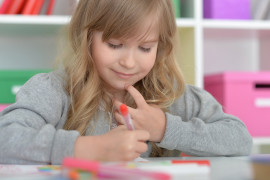 Cute little student girl at art class at school