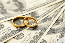 Golden wedding rings on one hundred dollars bill background