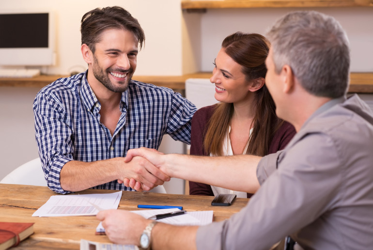 Handshake of a mature manager with a happy young couple at office. Businessmen handshake during meeting signing agreement.