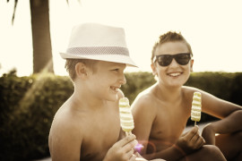 Two boys on a vacation eating ice cream outdoors