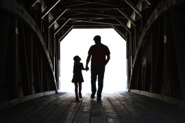 Father and daughter walking across a covered bridge holding hands.