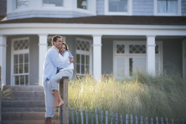 Couple embracing outside beach house
