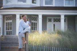 Couple embracing outside beach house